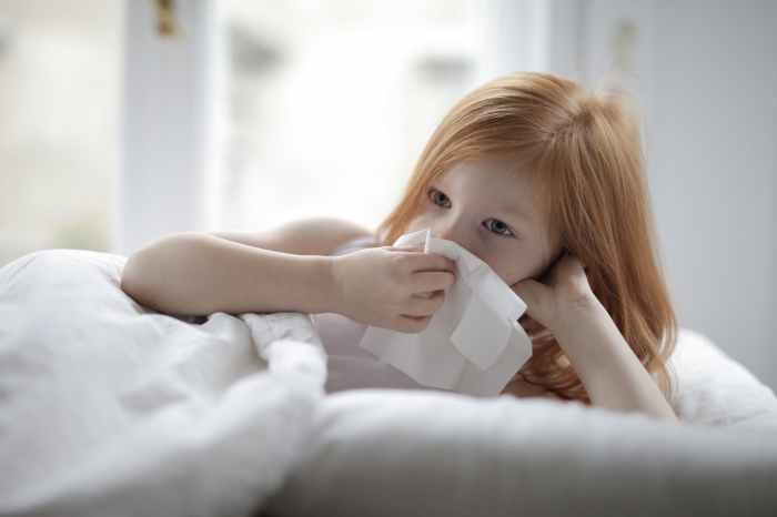 girl lying on bed holding tissue paper